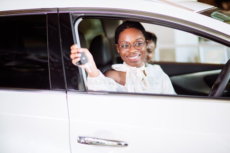 Mujer africana con su nuevo coche que muestra llave foto de archivo libre de regalías