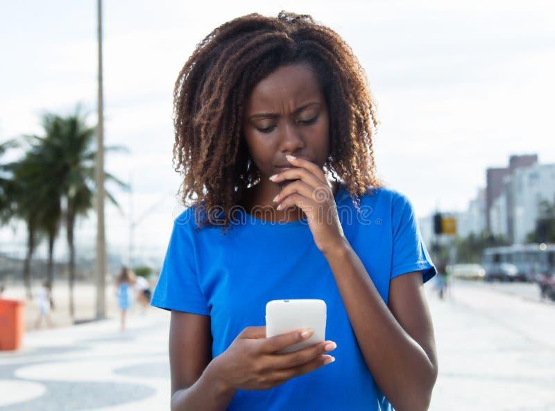Mujer africana de pensamiento en una camisa azul con el teléfono foto de archivo libre de regalías