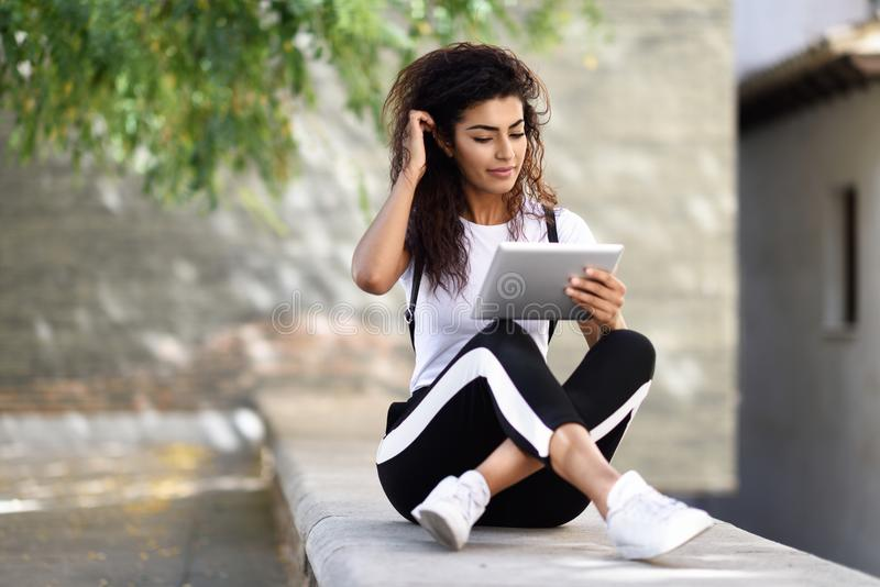 Mujer africana del norte joven con la mirada de su tableta digital hacia fuera fotografía de archivo