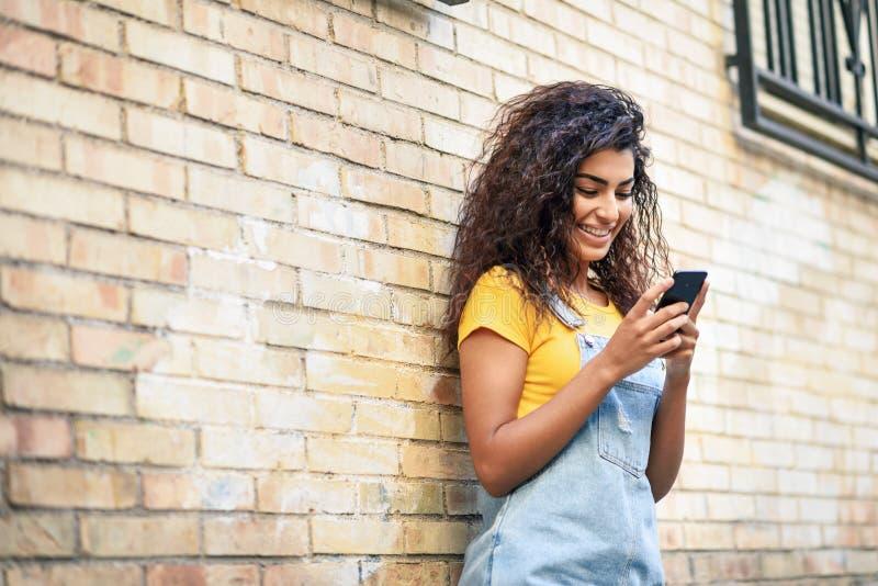 Mujer africana del norte joven que manda un SMS con su teléfono elegante al aire libre fotografía de archivo