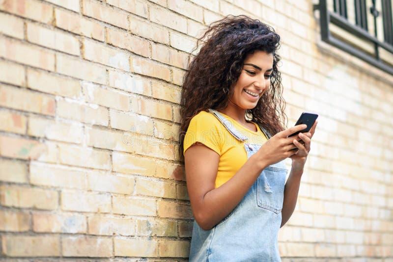 Mujer africana del norte joven que manda un SMS con su teléfono elegante al aire libre foto de archivo libre de regalías