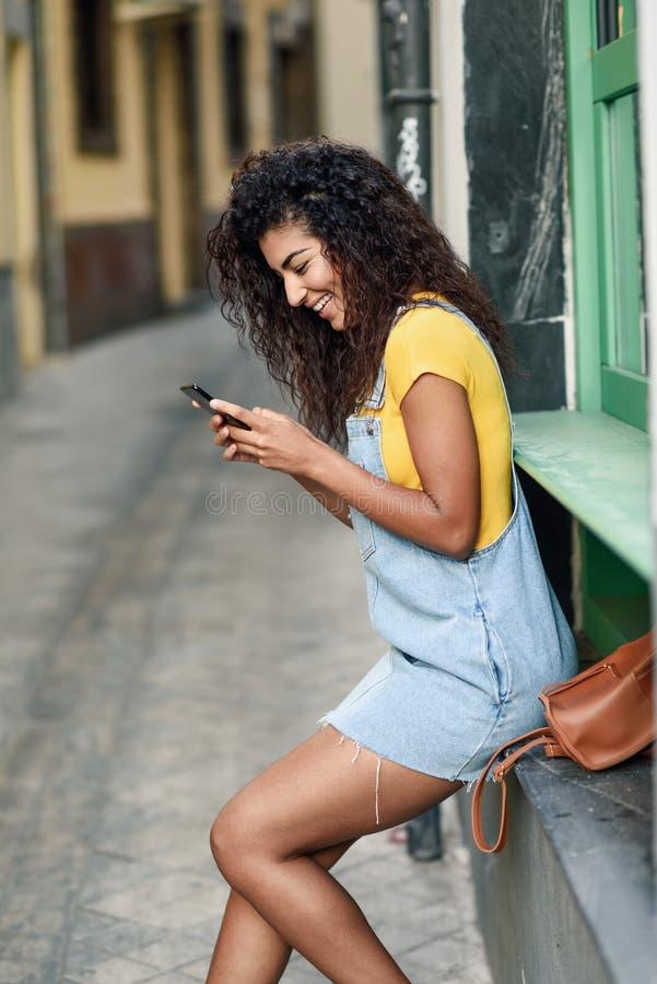 Mujer africana del norte joven que manda un SMS con su tel?fono elegante al aire libre fotografía de archivo libre de regalías