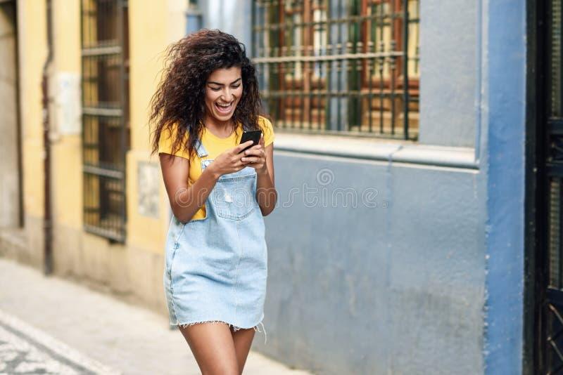 Mujer africana del norte que camina en el lookint de la calle en su p elegante foto de archivo