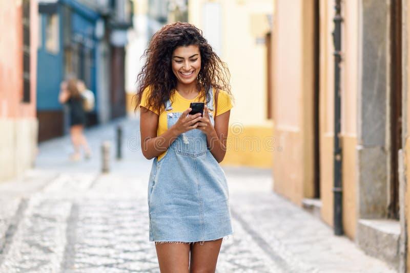 Mujer africana del norte que camina en la calle que mira su teléfono elegante imagenes de archivo