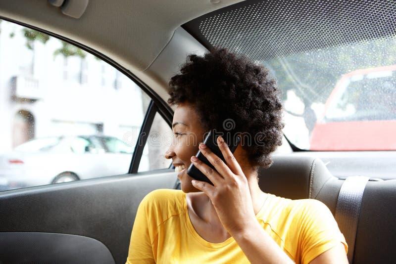 Mujer africana en el asiento trasero del coche que hace una llamada de teléfono fotografía de archivo