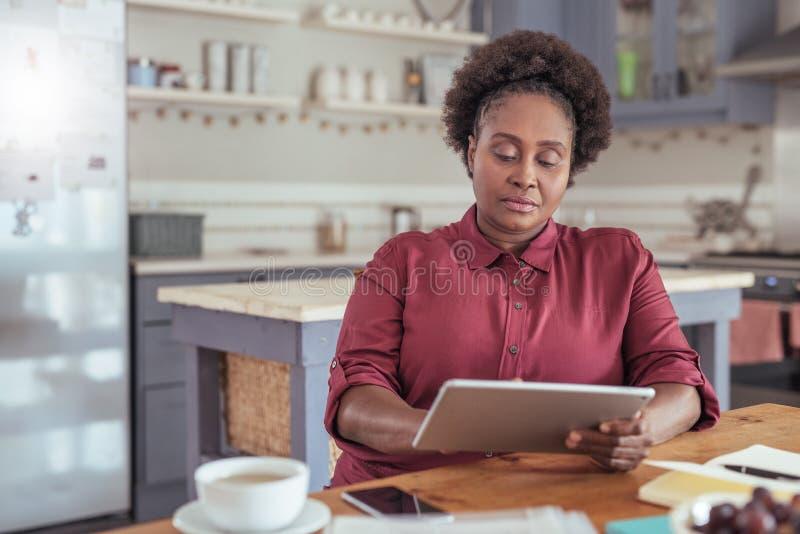 Mujer africana enfocada que trabaja en una tableta digital en casa imagen de archivo