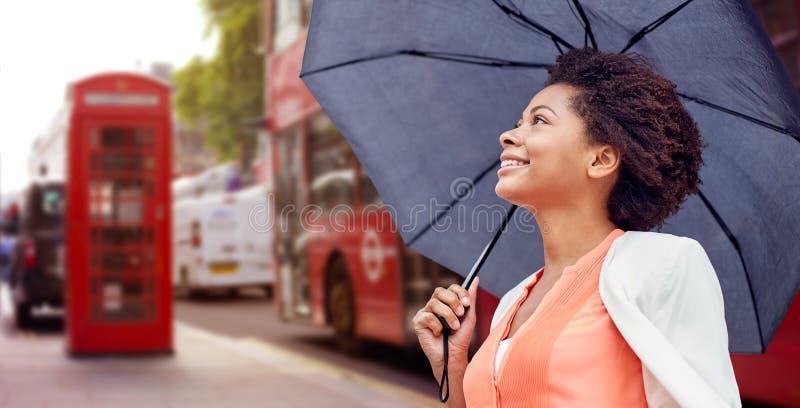Mujer africana feliz con el paraguas en la ciudad de Londres imagen de archivo