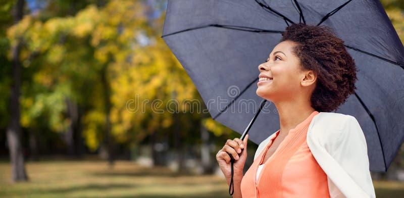 Mujer africana feliz con el paraguas en parque del otoño imágenes de archivo libres de regalías