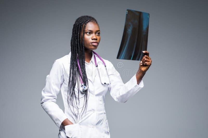 Mujer africana hermosa del doctor con la radiografía de pulmones, fluorography, roentgen en fondo gris Personales de atención san fotografía de archivo libre de regalías