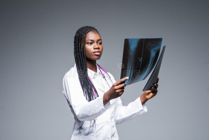 Mujer africana hermosa del doctor con la radiografía de pulmones, fluorography, roentgen en fondo gris Personales de atención san foto de archivo libre de regalías