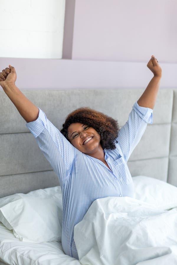 Mujer africana hermosa en el stylishpajama que estira mientras que se sienta en la cama fotos de archivo