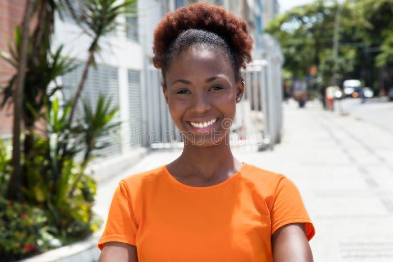 Mujer africana hermosa en una camisa anaranjada foto de archivo libre de regalías