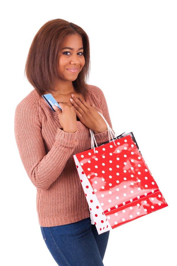 Mujer africana hermosa que sostiene una tarjeta y los panieres de crédito imagenes de archivo