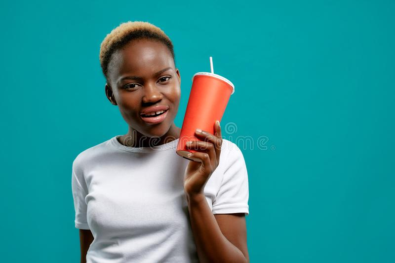 Mujer africana hermosa que sostiene y que muestra la taza roja de papel imagen de archivo libre de regalías