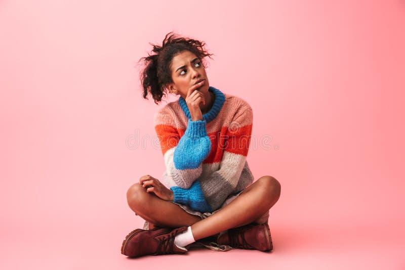 Mujer africana joven aburrida cansada que presenta sobre fondo rosado de la pared fotografía de archivo libre de regalías