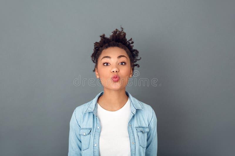 Mujer africana joven aislada en cámara que se besa de la pared de la forma de vida diaria casual gris del estudio fotos de archivo