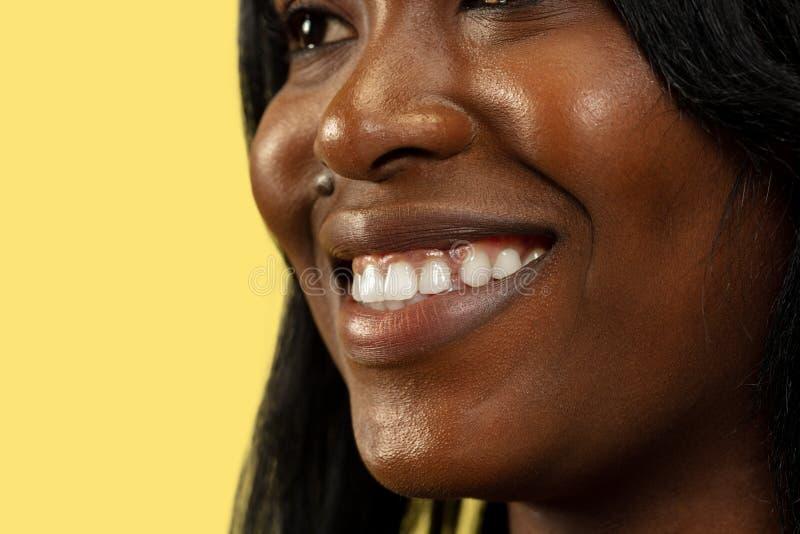 Mujer africana joven aislada en el fondo amarillo del estudio, expresión facial imagen de archivo