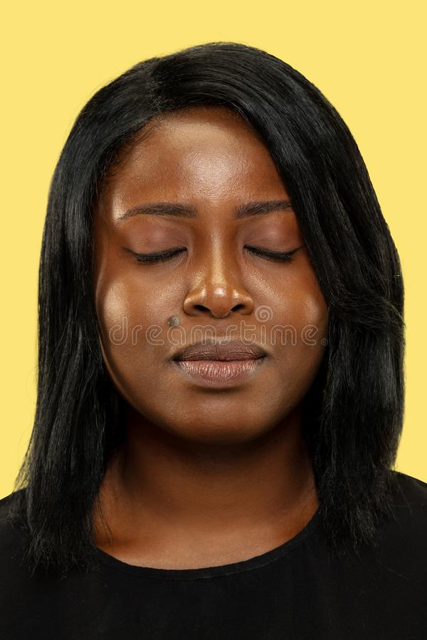 Mujer africana joven aislada en el fondo amarillo del estudio, expresión facial fotos de archivo libres de regalías
