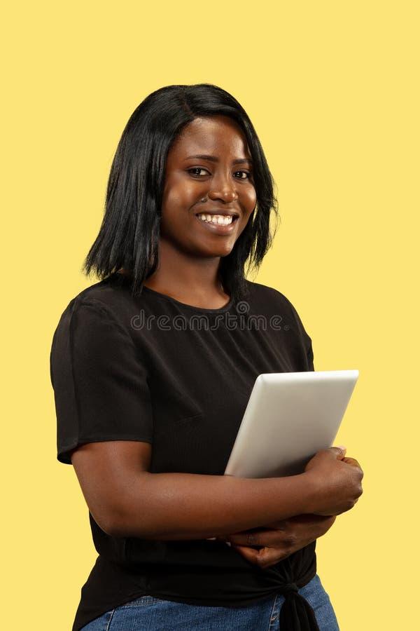 Mujer africana joven aislada en el fondo amarillo del estudio, expresión facial fotografía de archivo libre de regalías