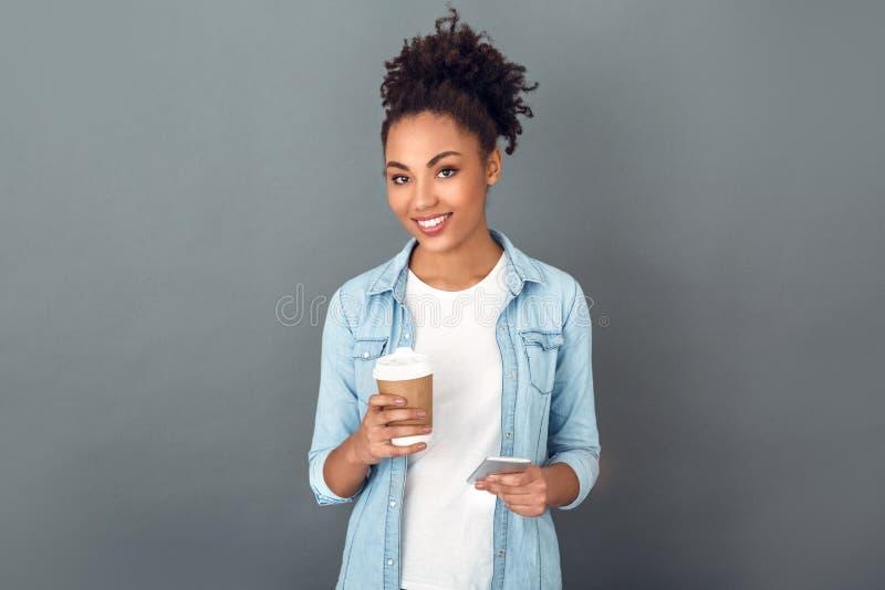 Mujer africana joven aislada en la forma de vida diaria casual del estudio gris de la pared que sostiene el café fotografía de archivo libre de regalías