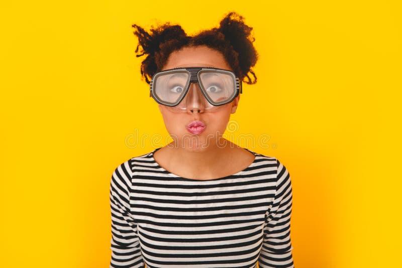 Mujer africana joven aislada en las lentes de la zambullida de la pared que llevan del estilo adolescente amarillo del estudio imagenes de archivo