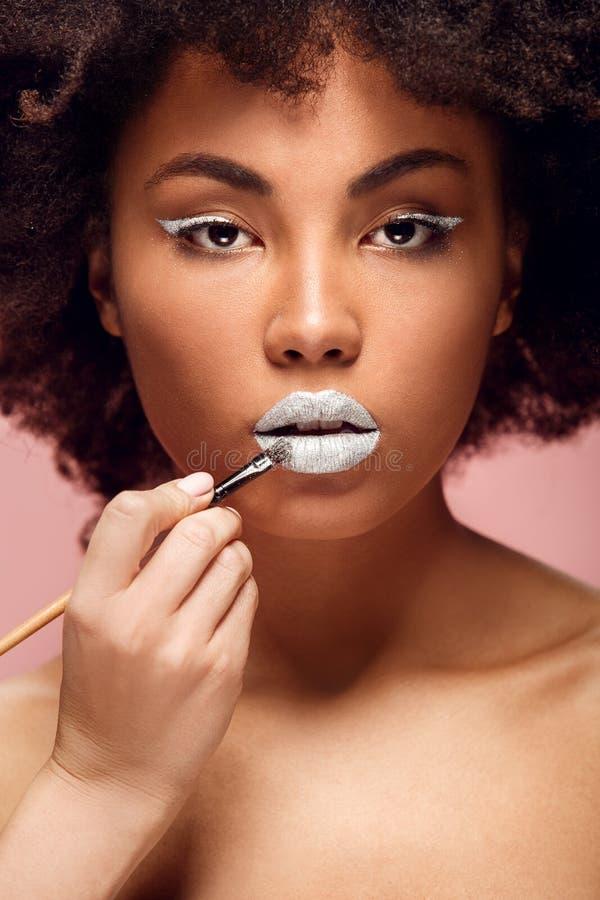 Mujer africana joven aislada en proceso elegante del maquillaje de la pared de la moda rosada del estudio fotos de archivo libres de regalías