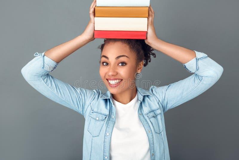 Mujer africana joven aislada en ratón de biblioteca diario casual de la forma de vida del estudio gris de la pared imágenes de archivo libres de regalías