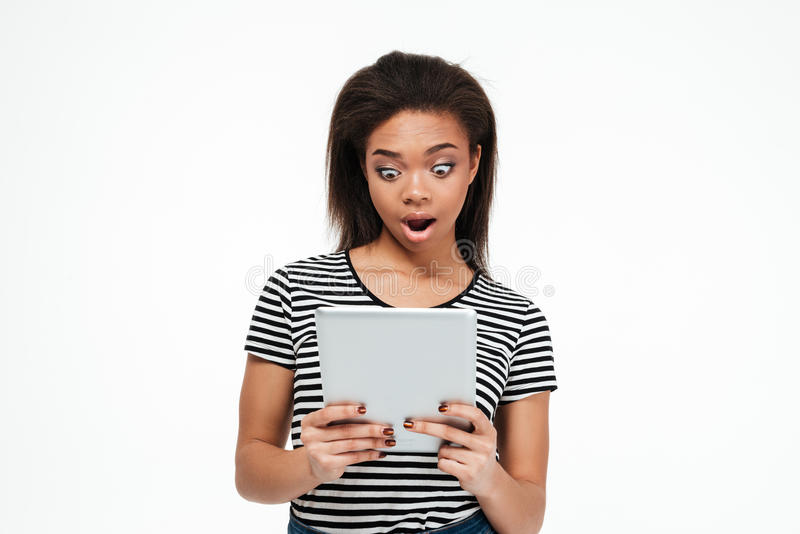 Mujer africana joven chocada que usa la tableta imágenes de archivo libres de regalías