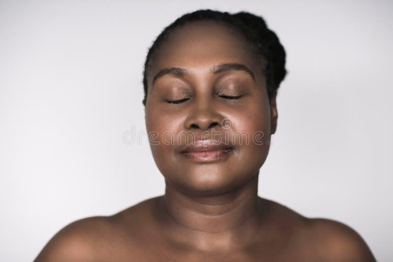 Mujer africana joven con la piel hermosa contra un fondo gris imágenes de archivo libres de regalías