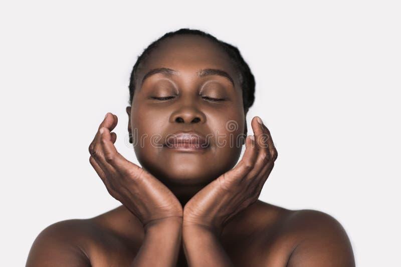 Mujer africana joven con la piel perfecta contra un fondo blanco fotos de archivo