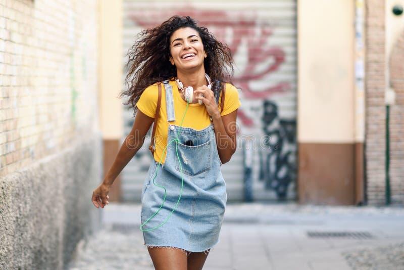 Mujer africana joven con los auriculares que camina al aire libre fotos de archivo