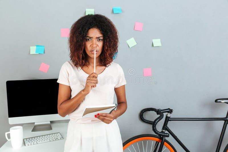 Mujer africana joven de pensamiento seria que sostiene el lápiz imagen de archivo