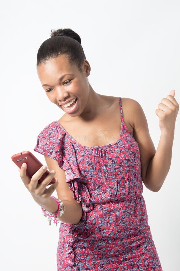Mujer africana joven emocionada sobre mensaje de texto imagen de archivo libre de regalías