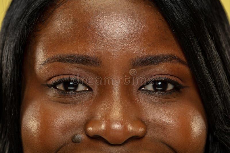 Mujer africana joven en el fondo amarillo del estudio, expresión facial imagen de archivo