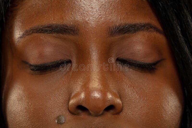 Mujer africana joven en el fondo amarillo del estudio, expresión facial imagenes de archivo