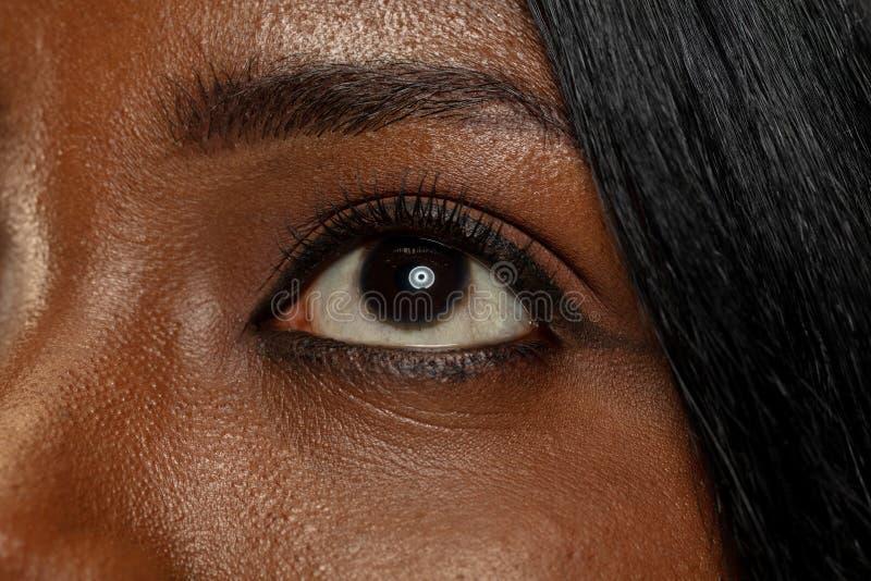 Mujer africana joven en el fondo amarillo del estudio, expresión facial fotografía de archivo