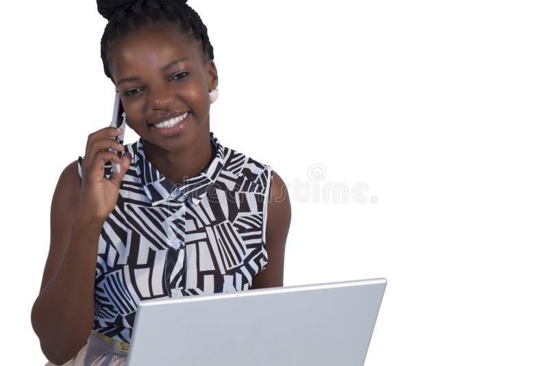 Mujer africana joven en el teléfono móvil imagenes de archivo
