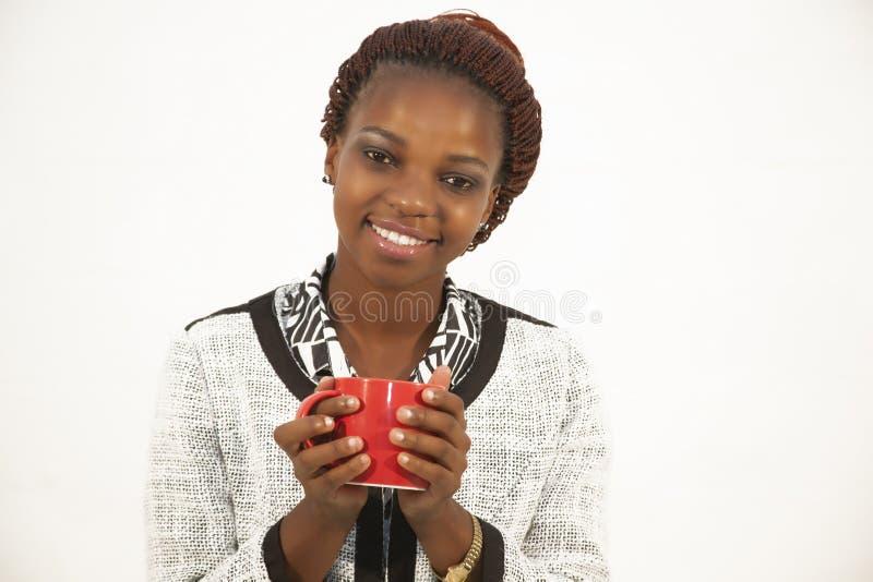 Mujer africana joven hermosa que sostiene una taza de café fotografía de archivo