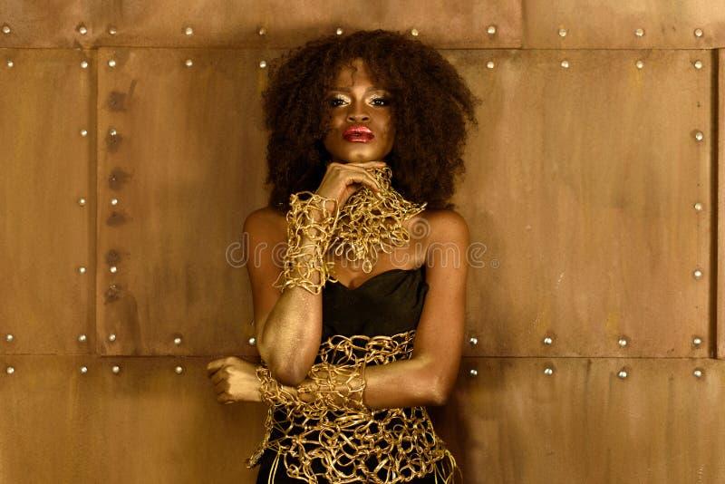 Mujer africana joven pensativa en maquillaje del oro y accesorios que llevan a cabo la mano en la barbilla, mirando la cámara imagen de archivo