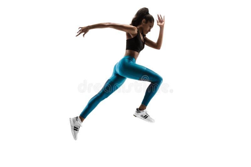 Mujer africana joven que corre o que activa aislada en el fondo blanco del estudio imágenes de archivo libres de regalías