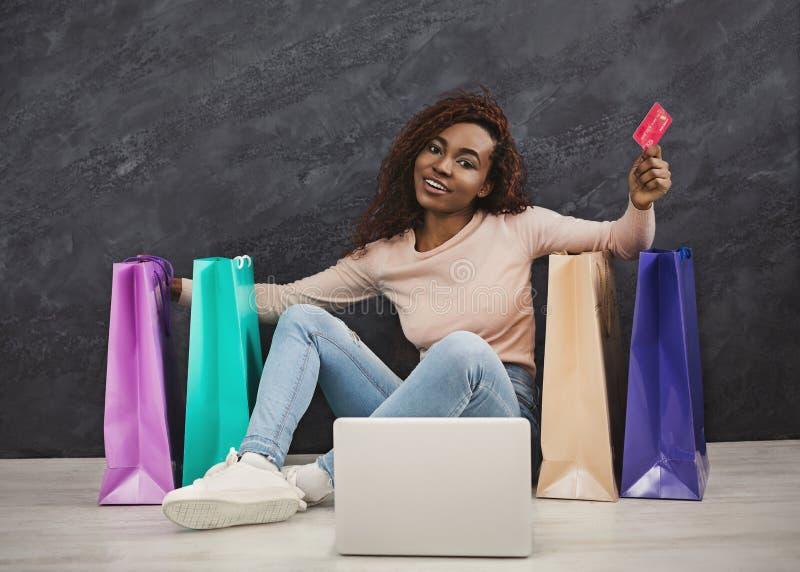 Mujer africana joven que hace compras en línea en casa fotografía de archivo libre de regalías