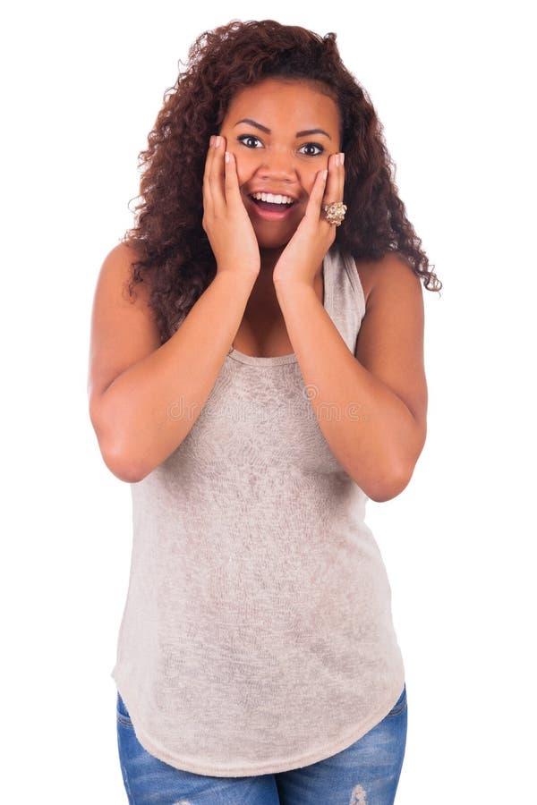 Mujer africana joven que parece sorprendida en el fondo blanco fotografía de archivo libre de regalías