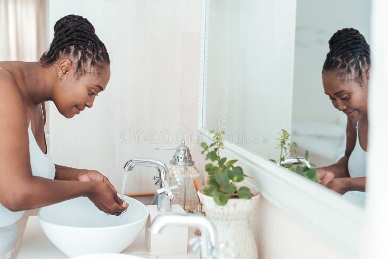 Mujer africana joven que se lava la cara en el fregadero del cuarto de baño imágenes de archivo libres de regalías