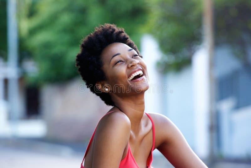 Mujer africana joven que se sienta al aire libre y que ríe fotografía de archivo libre de regalías