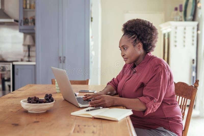 Mujer africana joven que sienta en casa el trabajo en un ordenador portátil fotografía de archivo libre de regalías