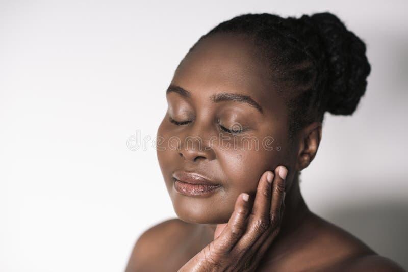 Mujer africana joven que toca su mejilla contra un fondo blanco imagenes de archivo