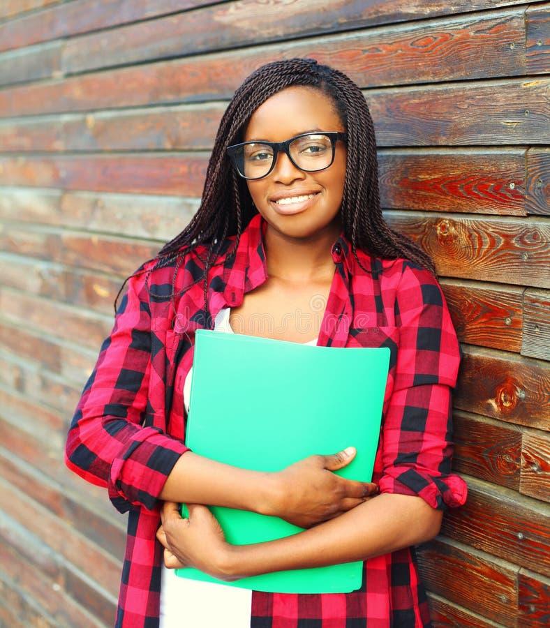 Mujer africana joven sonriente del retrato en los vidrios que sostienen la carpeta sobre fondo imagen de archivo