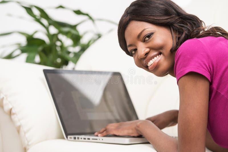 Mujer africana joven sonriente hermosa que miente en el sofá de cuero en casa imágenes de archivo libres de regalías