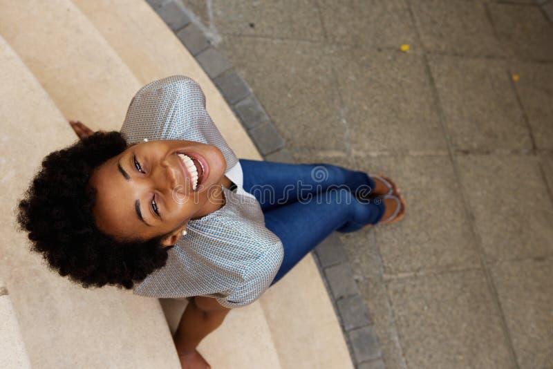 Mujer africana joven sonriente que se sienta en pasos y que mira para arriba imagenes de archivo
