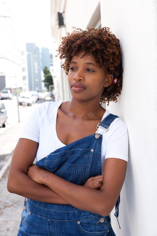 Mujer africana moderna que se inclina en la pared afuera foto de archivo